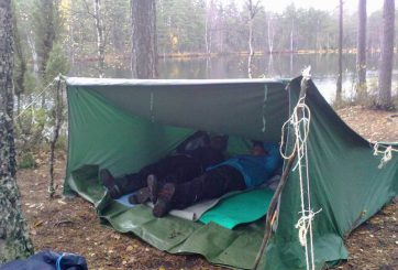 Spejarscouter som vilar efter att vindskyddet är rest